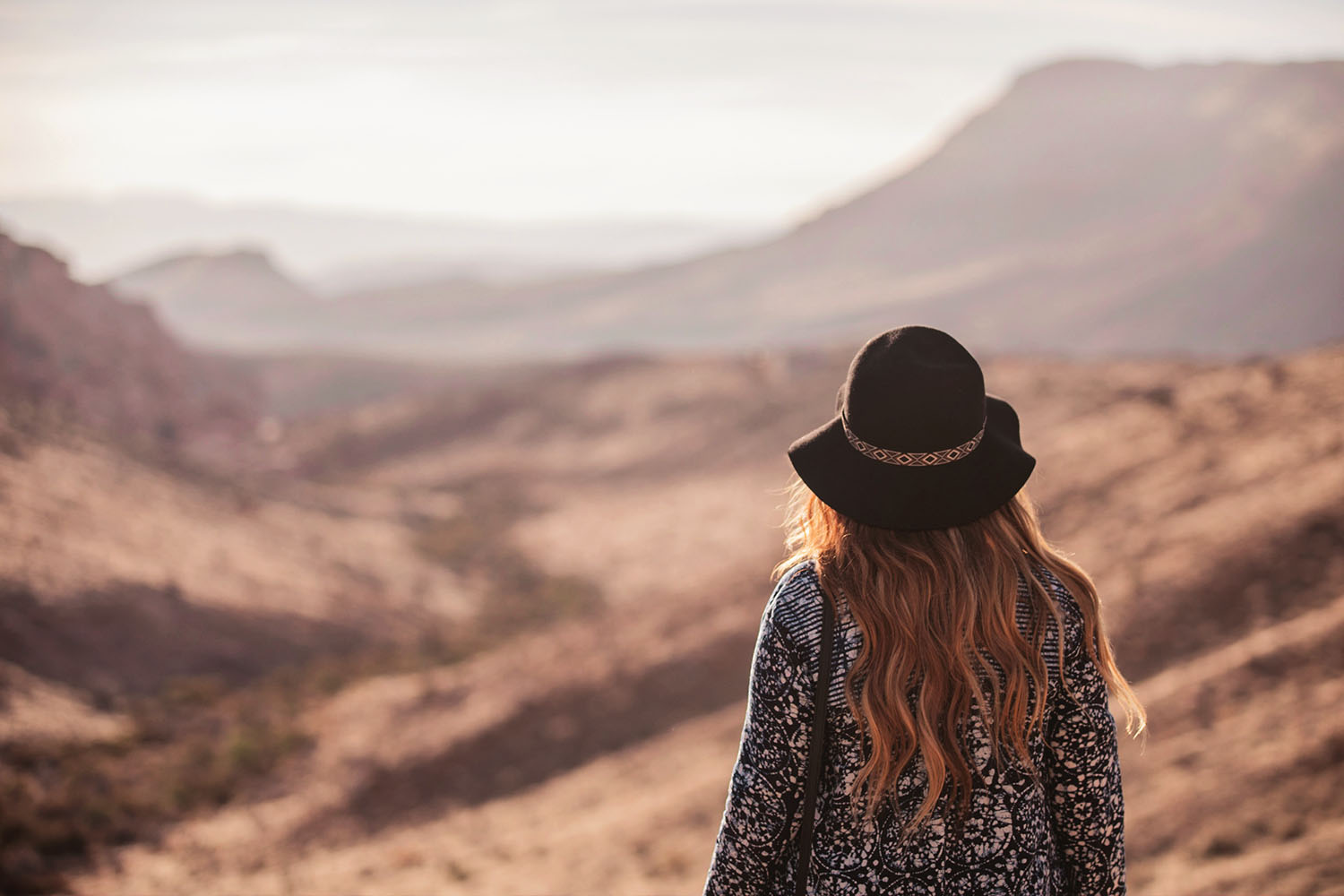 Girl with hair and long hair looking out over the Red Rock Canyon Sunrise