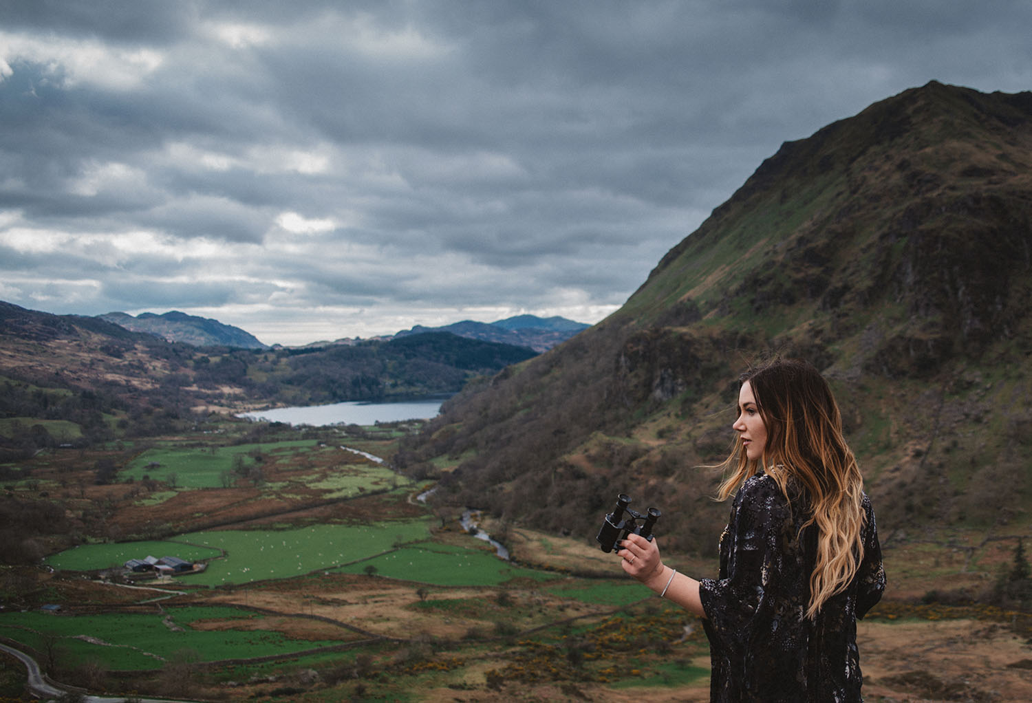 Girl with binoculars standing in front of Nant Gwynant Pass - A King Arthur: Legend of the Sword Filming Location in Wales