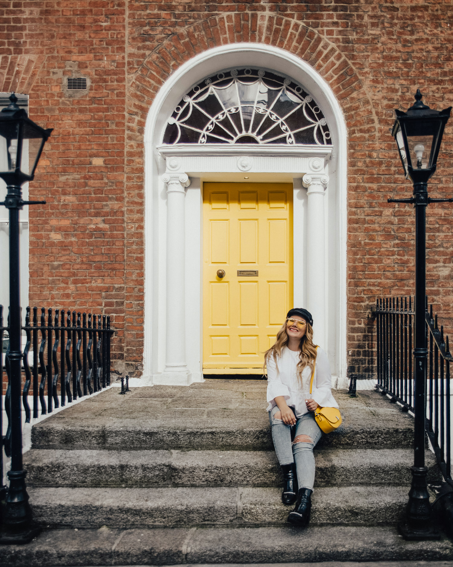 Woman with cap and yellow bag sitting by Georgian Yellow Door in Dublin, Ireland