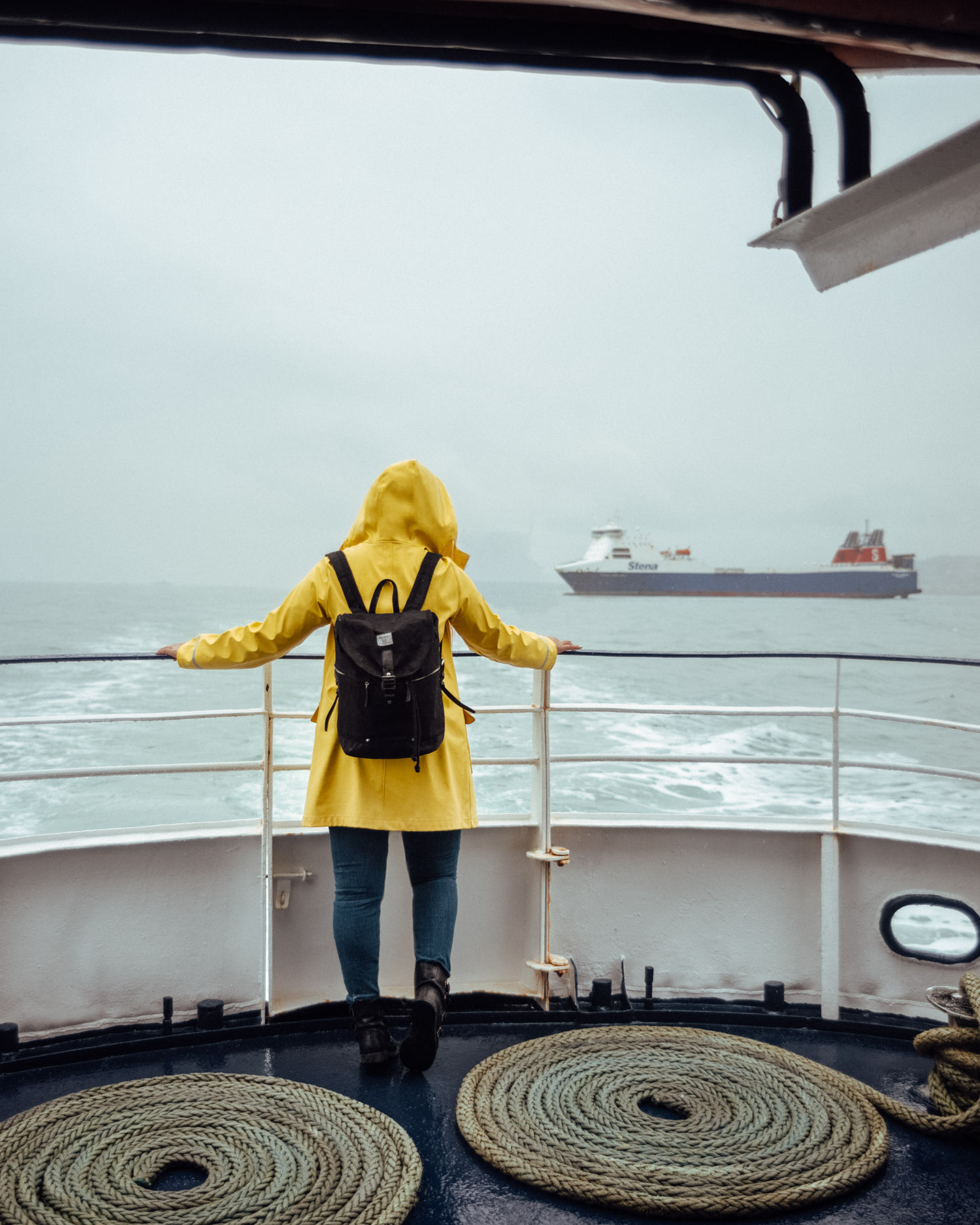 Dublin Bay Cruises to Howth | Woman with yellow raincoat standing on a boat in the rain