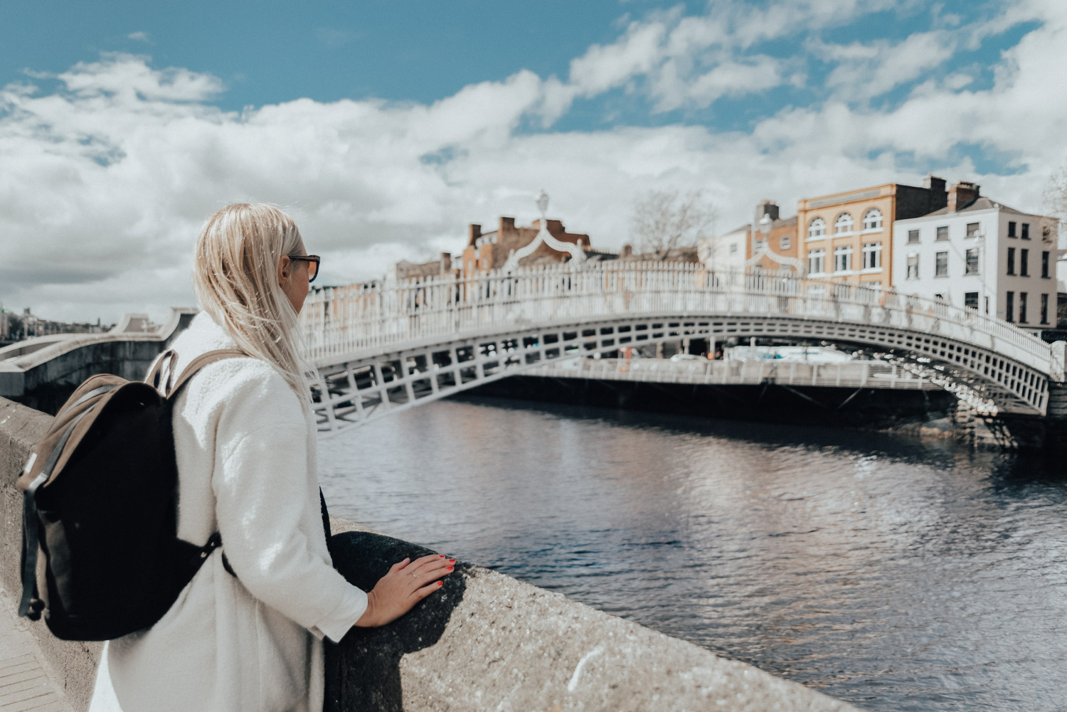 Woman in White Coat & Sandqvist bag standing by Ha'penny Bridge in Dublin