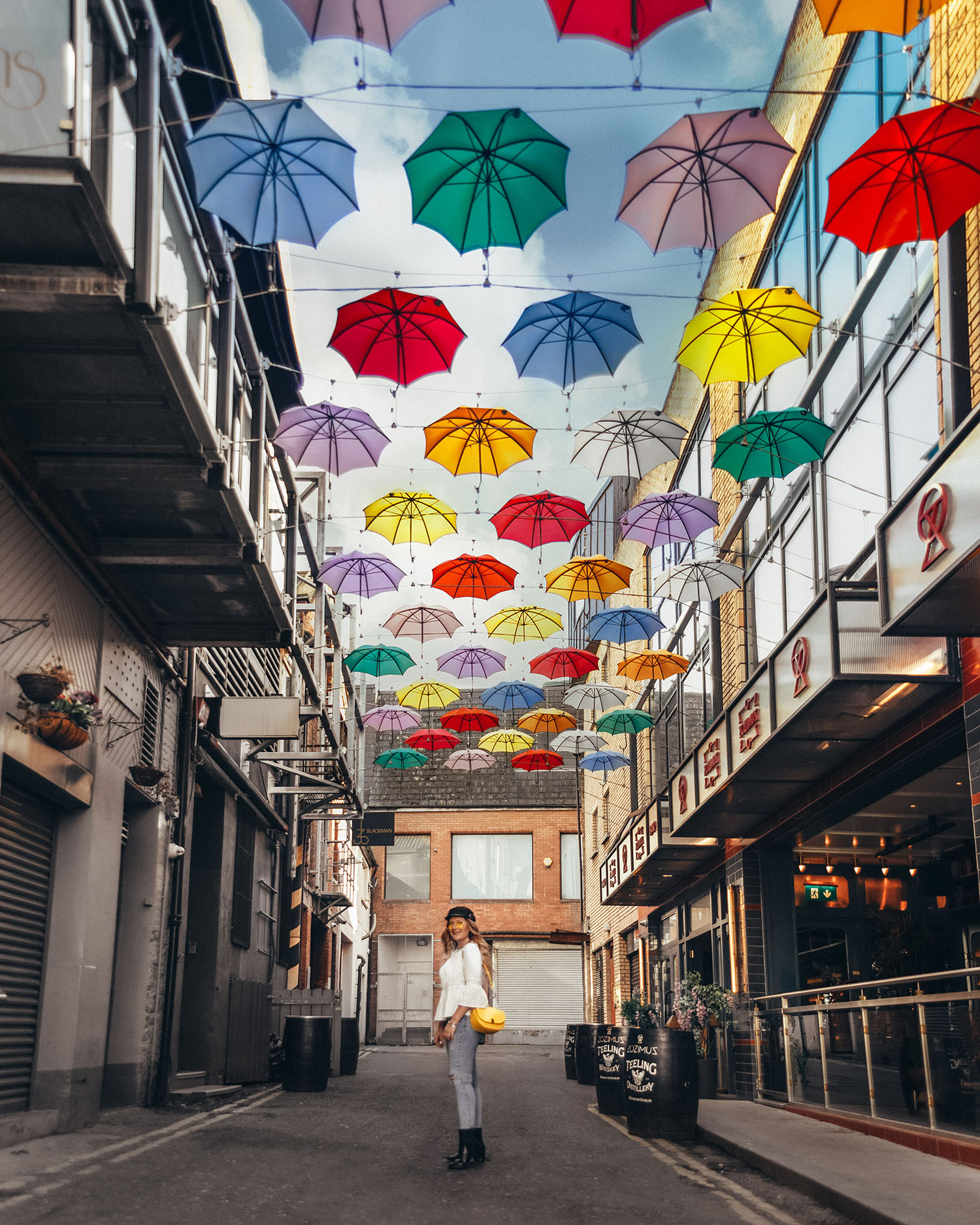 Woman Standing under a colorful roof of umbrellas by Zozimus Bar in Dublin, Ireland