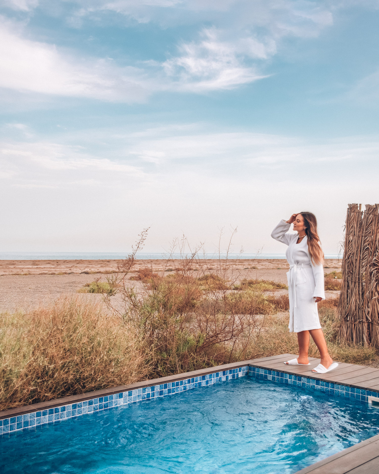 Woman in white bathrobe standing by private pool at Kingfisher Lodge, Sharjah