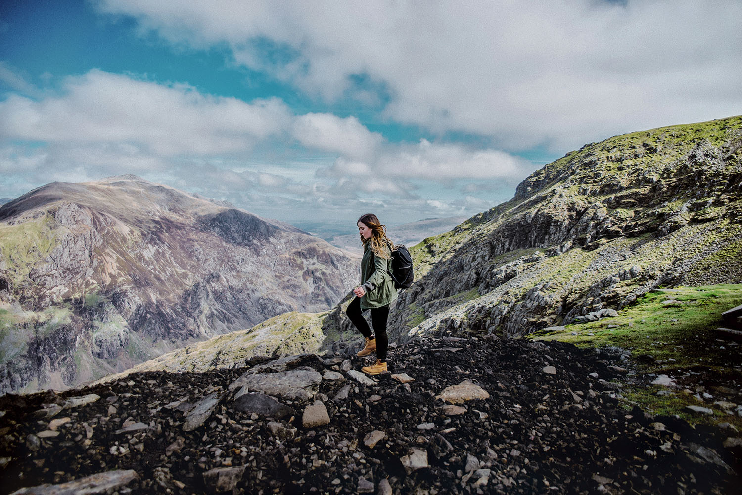Girl with backpack walking in Clogwyn, Snowdonia National Park in Wales - The Best Place to Visit in The UK