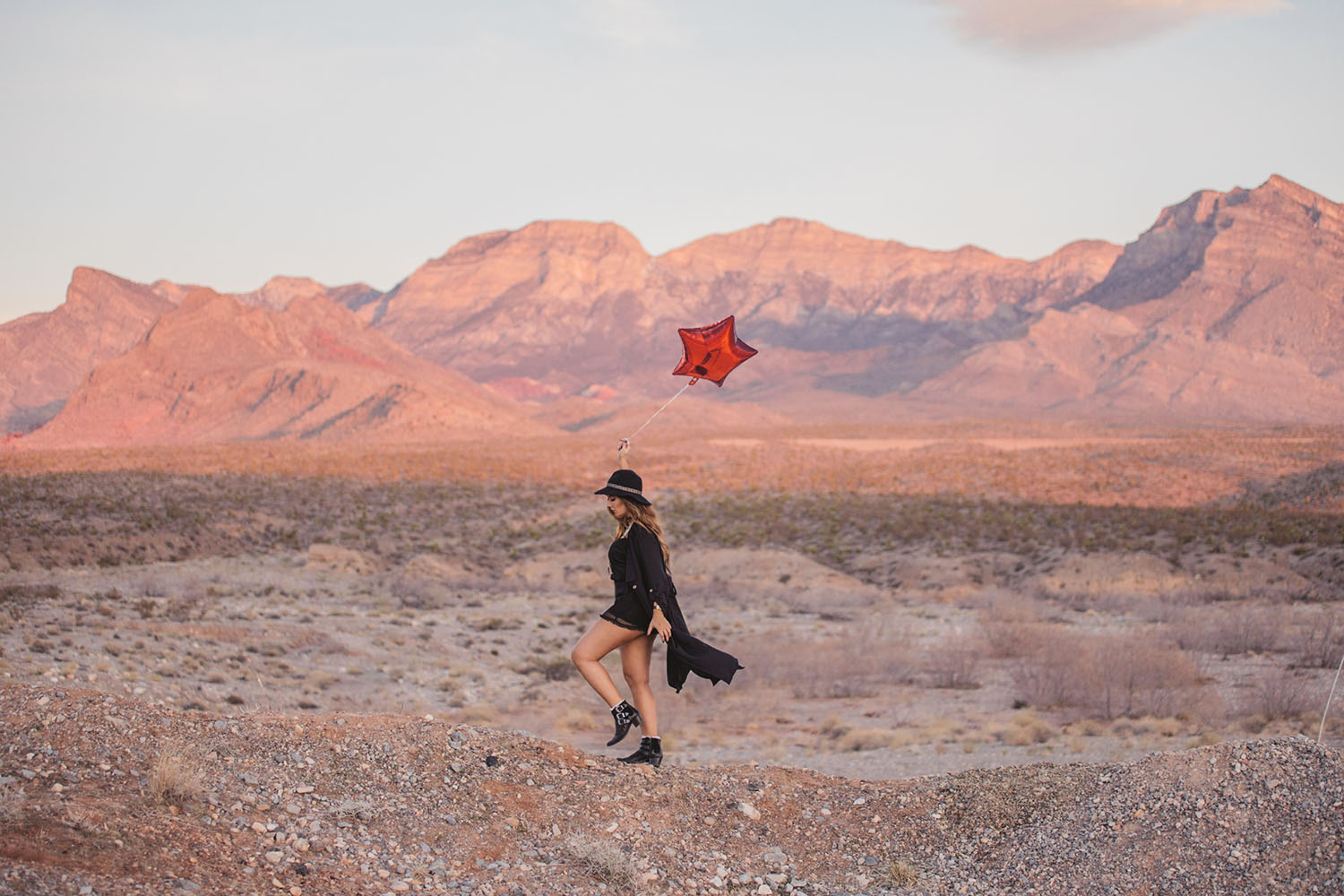 Girl walking with red balloon in sunrise in Red Rock Canyon, Las Vegas