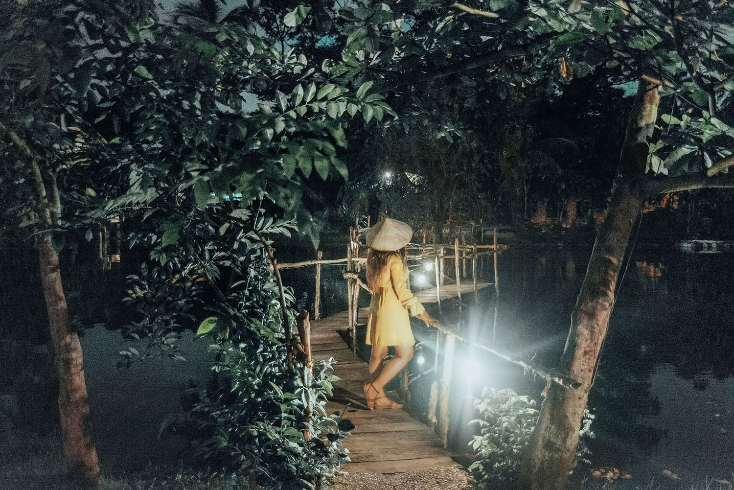 Woman in Yellow Dress with Vietnamese hat standing on bridge in Binh Quoi Village, Ho Chi Minh City, Vietnam