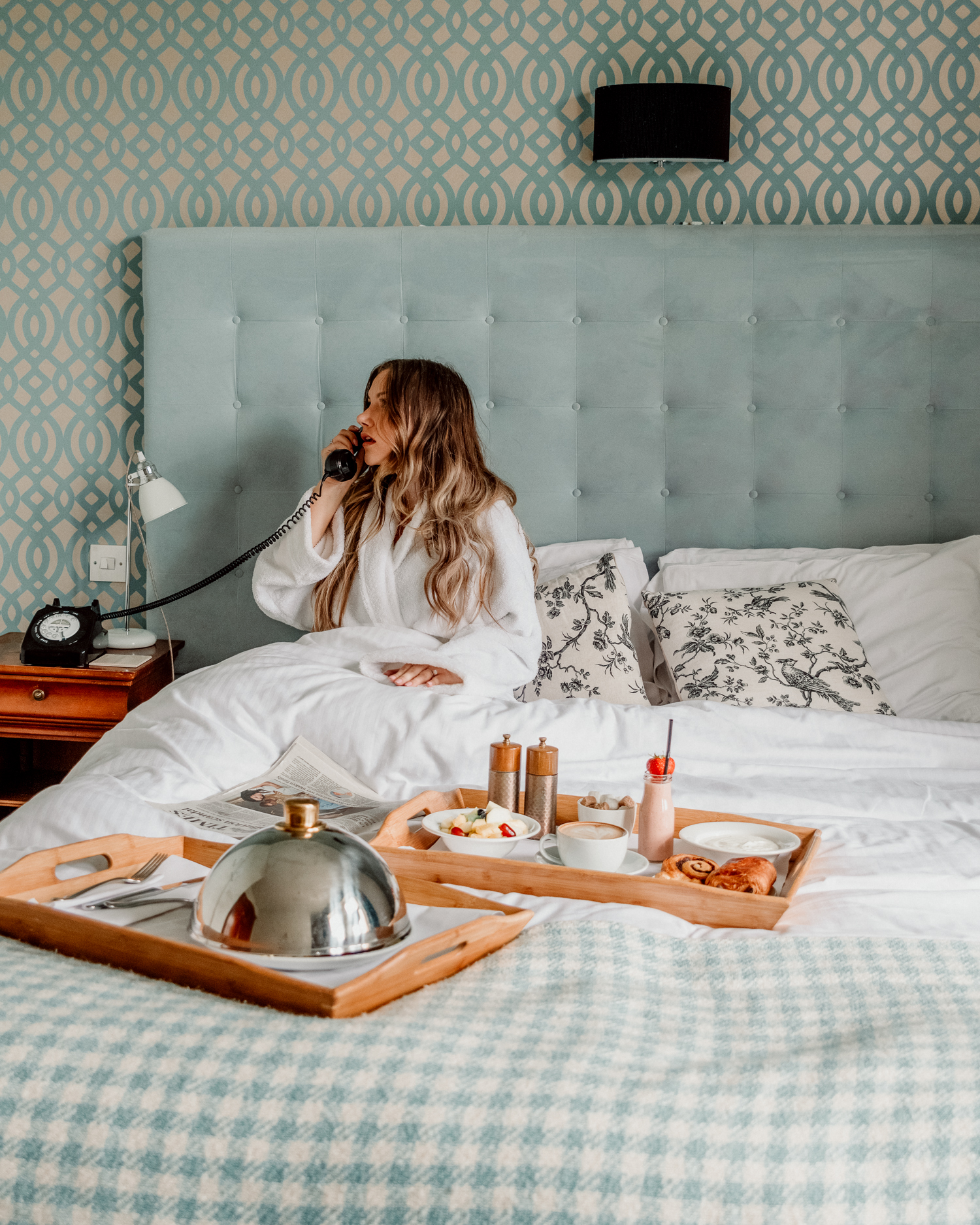 Woman in bath robe talking in telephone in bed at The Alverton Hotel in Cornwall, UK