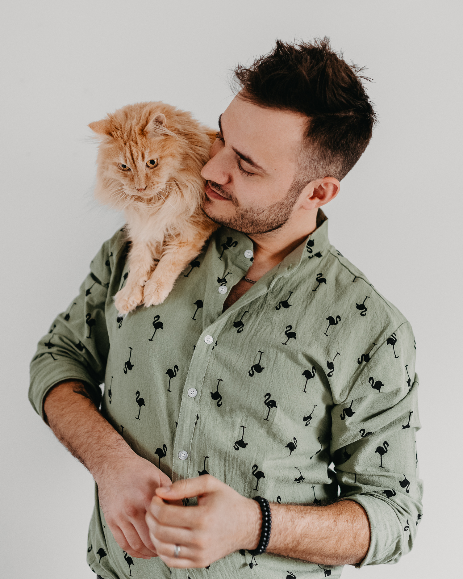Cute furry orange cat sitting on man's shoulder