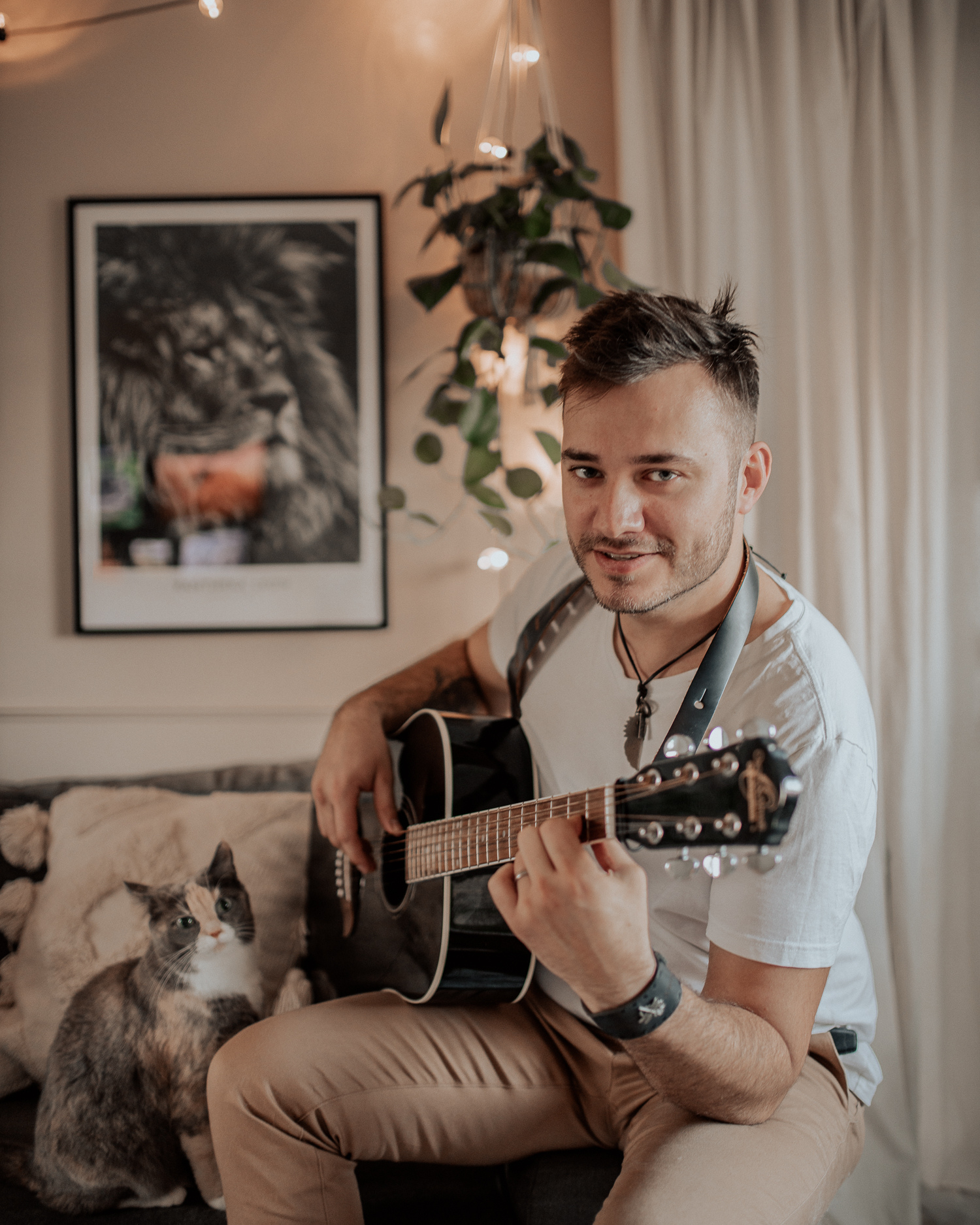 Man playing guitar at home with a cat by his side