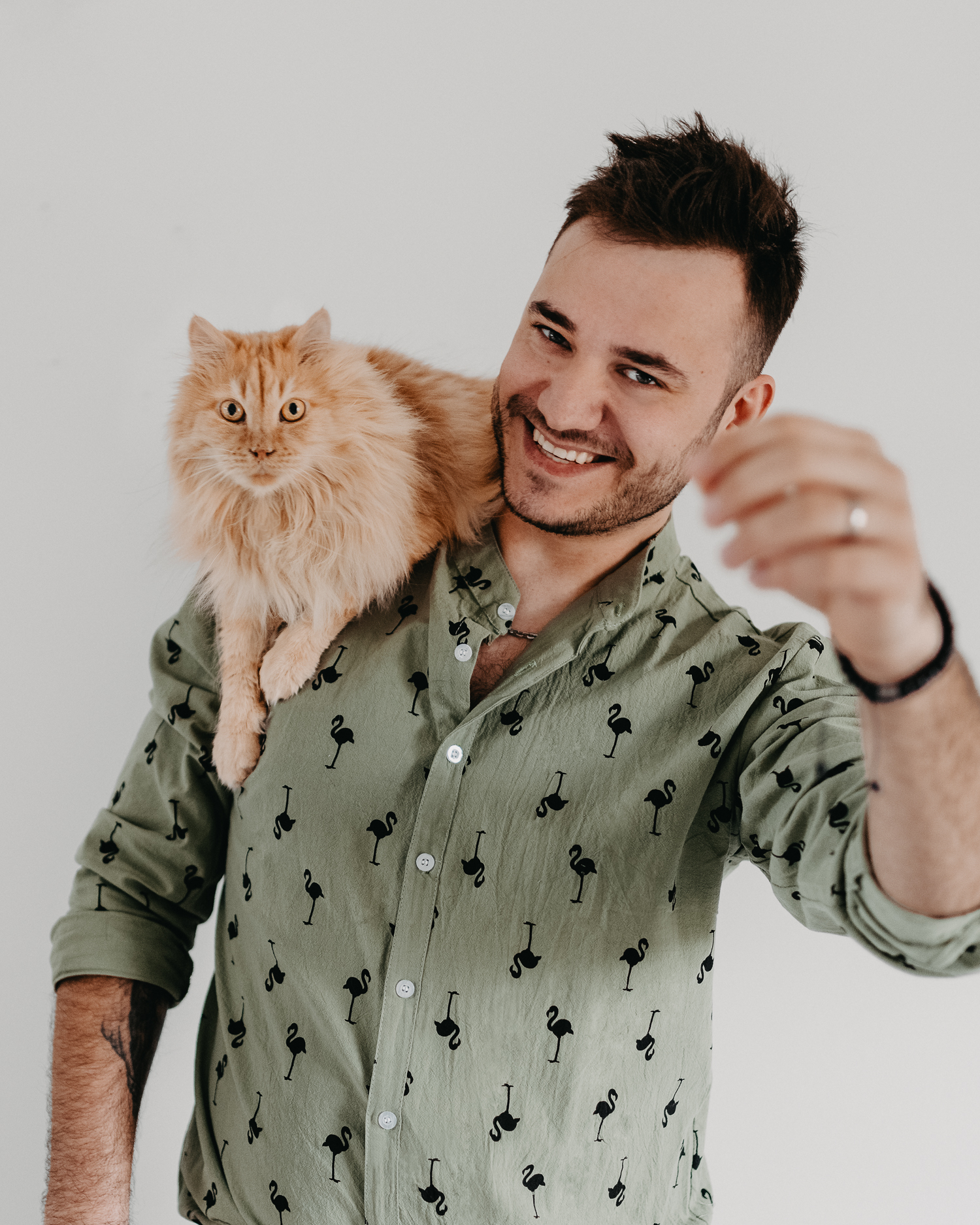 Cute orange cat sitting on man's shoulder