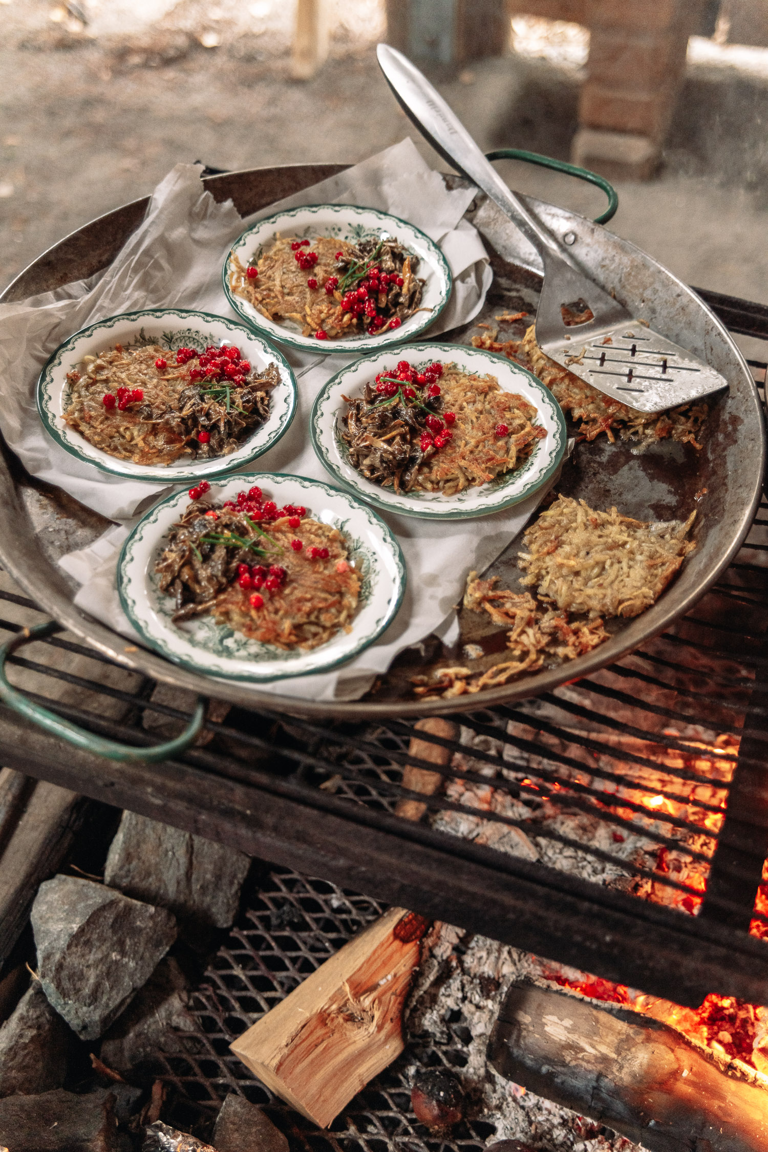 Hash browns, mushrooms and lingonberries are cooked over an open fire in Brevens Bruk, Örebro.